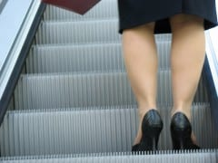Business woman on escalator